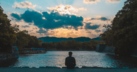 Rear View Of Man Sitting By Lake During Sunset 11115068619| 写真素材・ストックフォト・画像・イラスト素材|アマナイメージズ