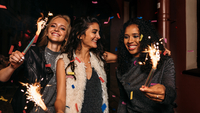 smiling friends holding lit sparklers in party