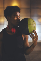man with headphones and basketball standing against wall