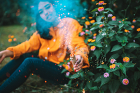 woman holding lit sparkler while sitting by flowering plants