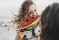 happy woman eating watermelon with girlfriend at beach