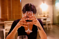 Young Woman Holding Wineglass While Sitting In Restaurant