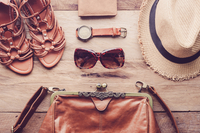 High Angle View Of Leather Purse With Sandals And Hat On Table