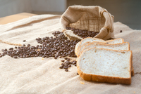 Close-up Of Bread And Coffee Beans On Table 11115081449| 写真素材・ストックフォト・画像・イラスト素材|アマナイメージズ