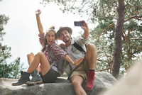 Happy Friends Taking Selfie While Sitting On Rock In Forest