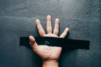 Cropped Hand Of Person With Adhesive Tape On Wall