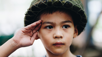 Close-up Of Cute Boy Wearing Helmet Looking Away While Saluting Outdoors 11115083525| 写真素材・ストックフォト・画像・イラスト素材|アマナイメージズ