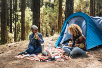 Mother And Daughter Having Food And Drink Against Tent In Forest
