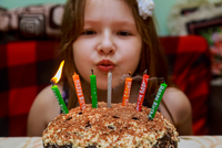 Close-up Portrait Of Smiling Girl Sitting By Cake At Home