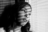 Close-up Of Lonely Girl Looking Through Window Blinds At Home