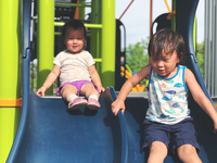 Siblings On Slides At Playground