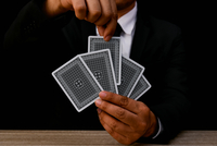 Midsection Of Man Holding Playing Cards Against Black Background