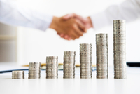 Cropped Image Of Businessmen Shaking Hands With Stack Of Coins On Table In Office