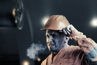 Tired Manual Worker Wearing Hardhat In Factory
