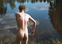 Rear View Of Naked Man Standing By Lake