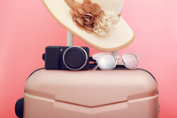 Luggage With Hat And Camera Against Pink Background