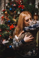 Young Woman Kissing Cat While Standing Against Christmas Tree At Home