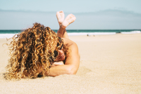 Woman With Curly Hair Relaxing On Beach