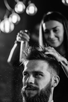 Close-up Of Woman Spraying On Man Hair At Shop