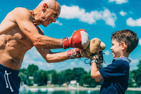 Shirtless Grandfather With Grandson Boxing Against Sky