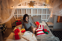 Woman With Gift Boxes Sitting On Bed At Home During Christmas