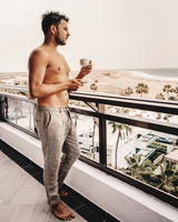 Side View Of Shirtless Handsome With Coffee Looking At Sea From Balcony