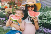 Pregnant Mother And Son Eating Watermelons While Sitting Against Plants
