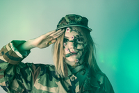 Close-up Portrait Of Young Woman In Army Costume Saluting While Standing Against Blue Background 11115124428| 写真素材・ストックフォト・画像・イラスト素材|アマナイメージズ