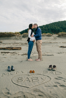 Full Length Of Pregnant Couple Kissing By Shoes And Text On Sand Against Sky