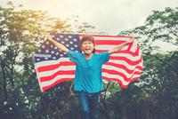 Happy Teenage Girl With American Flag Against Trees