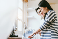 Smiling Man Looking At Woman Washing Plate In Kitchen
