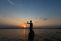 Silhouette Of Man Throwing Fishing Net While Standing In Boat On Sea Against Sky During Sunset