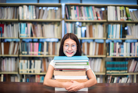 Portrait Of Smiling Female Student With Stack Books On Table In Library