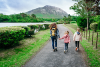 Rear View Of Woman With Daughters Walking On Road