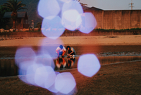 Friends Crouching By Lake With Defocused Lights In Foreground During Sunset