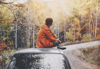 Side View Of Man Sitting On Car In Forest During Autumn