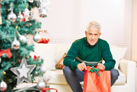 Portrait Of Senior Man Holding Christmas Gift While Sitting On At Home