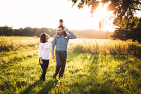 Happy Family On Grass In Park During Sunset