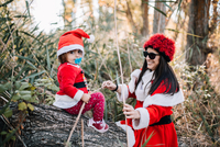 Cute Baby Girl With Mother Wearing Santa Costume In Forest