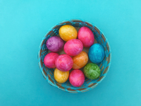 Close-up Of Multi Colored Easter Eggs In Basket Over Blue Background