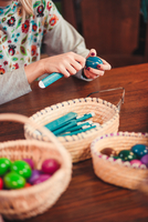 Midsection Of Woman Making Easter Eggs On Table
