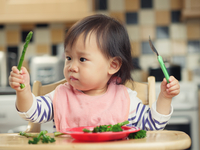 Baby Girl With Vegetables Sitting On High Chair At Home
