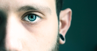 Close-up Portrait Of Man With Blue Eye Against Black Background