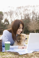 パソコンを操作する女性と犬 28204000085| 写真素材・ストックフォト・画像・イラスト素材|アマナイメージズ