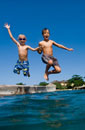 Two children jumping off platform into the sea
