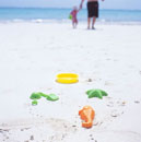 Father and daughter walking on the beach,plastic toys in f