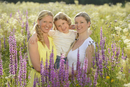 Close-up of a woman with her daughter and her mother in a flower meadow in summer, Bavaria, Germany.