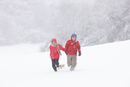 Boy and Girl Walking Through Snow Pulling Sledge
