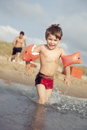 Smiling little boy running with his water wings into the sea