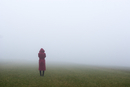 Austria, one teenager standing alone in park, fog